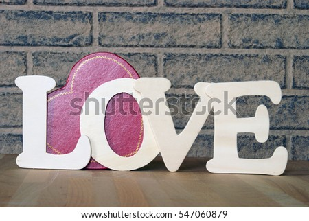 A handmade word of love using wood cuts and a lovely heart shaped box on the table as well for a romantic display of affection.