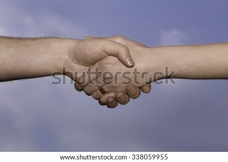 A handshake between a man and a woman, the woman is wearing a wedding ring. - stock photo