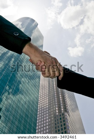 A handshake between a man and woman with tall beautiful glass towers of commerce in the background. - stock photo