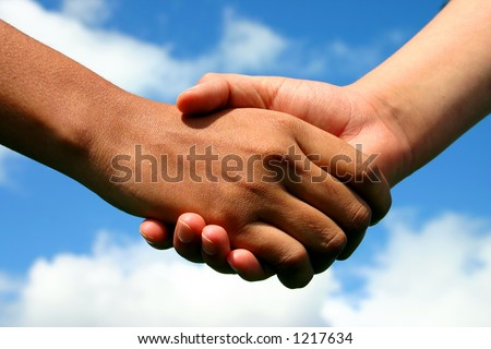 A handshake between an Indian lady and white boy symbolising friendship across gaps of race, age and gender - stock photo