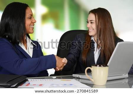 A handshake between two female co-workers in the office - stock photo