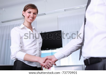 a handshake by a young businesswoman in office - stock photo