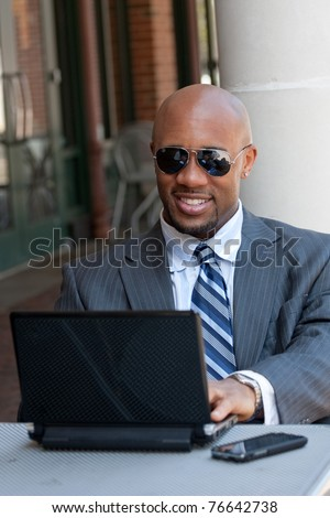 A handsome African American business man in his early 30s working on his laptop or netbook computer with his cell phone nearby. - stock photo
