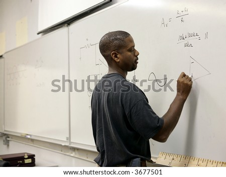 A handsome african-american student doing trigonometry at the board. - stock photo