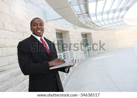 A handsome african business man on laptop computer at office building - stock photo