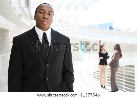 A handsome african business man with co-workers in background - stock photo