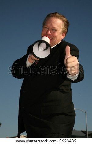 A handsome and friendly Business man speaks through a Megaphone to Get Your Message accross to the masses - stock photo