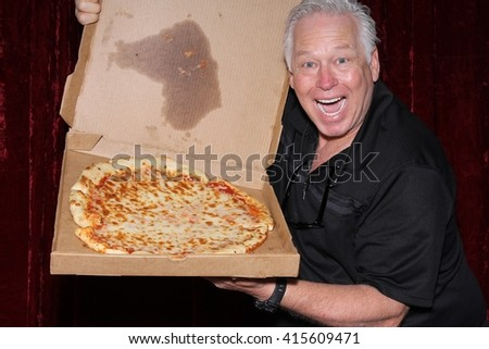A handsome and happy man holds a Pizza Box with a pizza inside while posing for photos in a Photo Booth. Photo Booths are popular for Birthdays, Weddings, and all parties indoors or outside. - stock photo