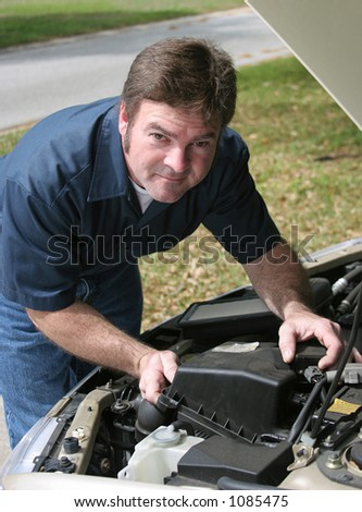 A handsome auto mechanic checking under the hood of a car.  Vertical