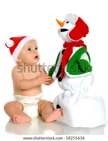 A handsome baby boy in a Santa hat, enthralled by a toy snowman.  Isolated on white. - stock photo