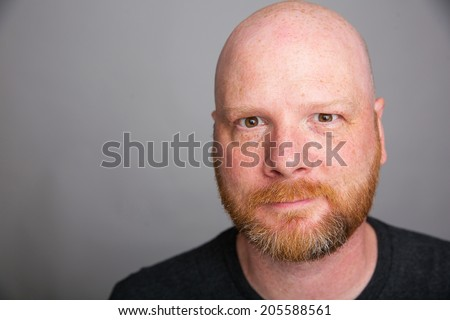 A handsome bald man with a red haired beard