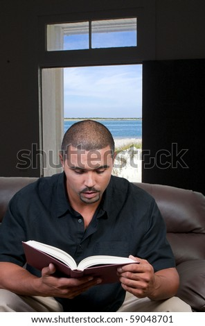 A handsome black man reading a book - stock photo