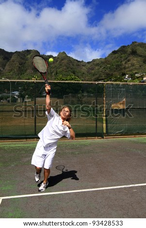 A handsome blonde tennis player makes a solid serve over the net - stock photo