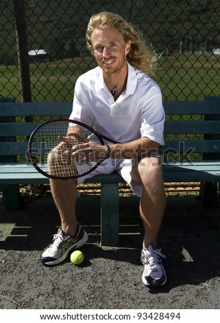A handsome blonde tennis player sits on the bench on the sidelines and smiles - stock photo