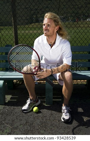 A handsome blonde tennis player watches the court from the sidelines - stock photo