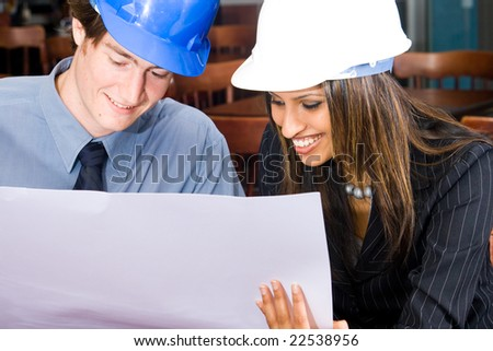 A handsome business construction manager and indian female construction worker in a cafe looking at blueprint - stock photo