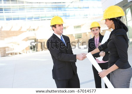 A handsome business man handshake with construction woman at office building - stock photo