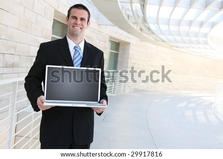 A handsome business man holding a laptop computer at office - stock photo