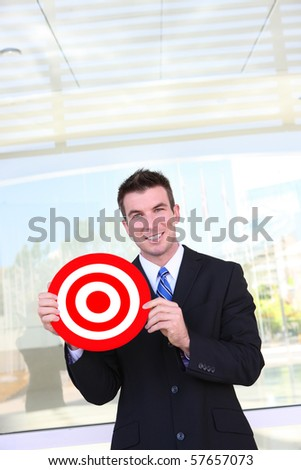 A handsome business man holding target at office - stock photo