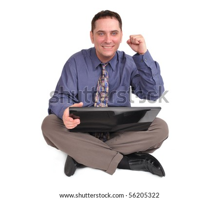 A handsome business man is sitting on the floor and holding a laptop internet computer. His hand is in the air and he is excited and happy. The background is isolated and white.