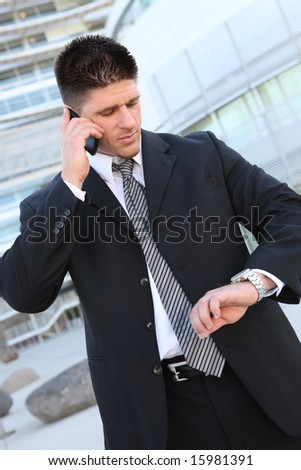 A handsome business man looking at watch and talking on cell phone - stock photo