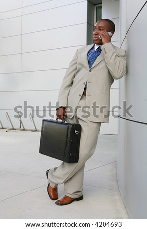 A handsome business man on the phone outside his office - stock photo