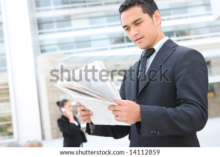 A handsome business man reading the newspaper at office building - stock photo