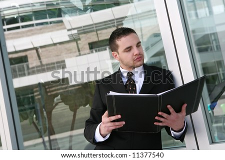 A handsome business man reviewing his notes at company