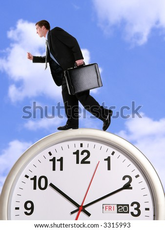 A handsome business man running on a large clock in th clouds - stock photo