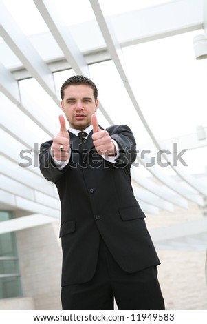 A handsome business man showing success with thumbs up