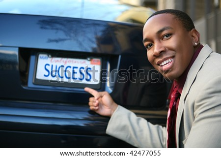 A handsome Business Man with car license plate success (Fictional License Plate) - stock photo