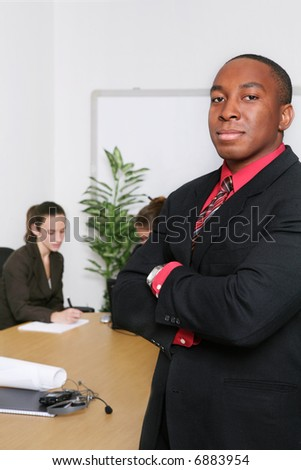A handsome business man with his team in the office