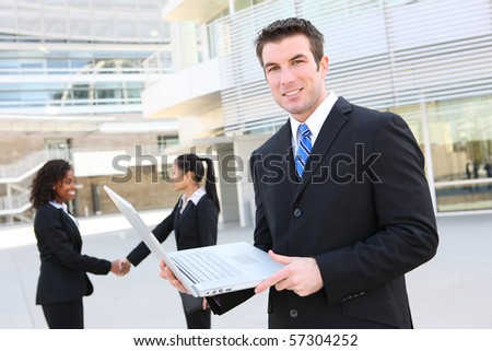 A handsome business man with laptop computer and team in background