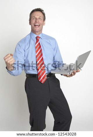 A handsome business punches the air in celebration at receiving good news on his laptop - stock photo