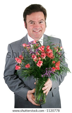 A handsome businessman holding a bouquet of roses for his wife, girlfriend, or secretary. - stock photo