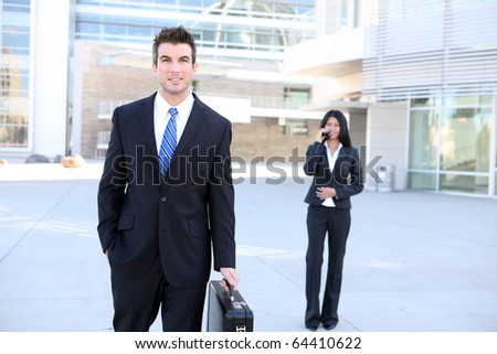 A handsome caucasian man at the office with woman co-worker in background