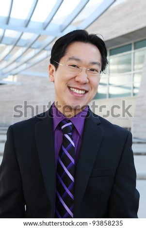 A handsome Chinese business man smiling at the office - stock photo
