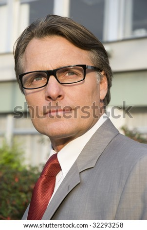 A handsome clever looking businessman wearing spectacles.