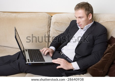 A handsome confident young man working on a laptop