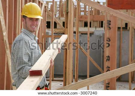 A handsome construction man carrying some wood - stock photo