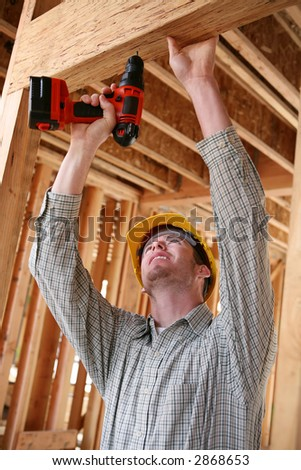 A handsome construction man using a drill to secure a beam - stock photo