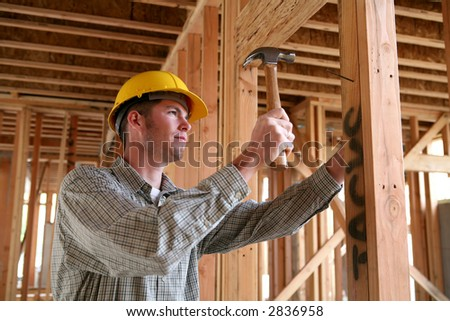 A handsome construction man using a hammer to nail together wood - stock photo