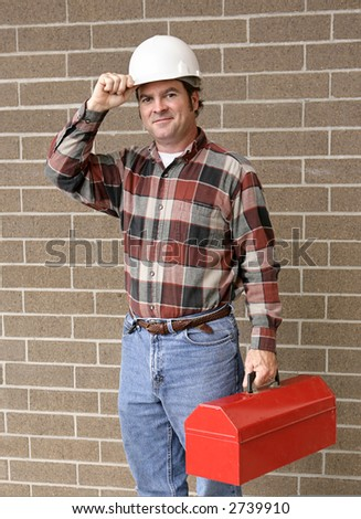 A handsome construction worker carrying his toolbox and tipping his hard hat. - stock photo