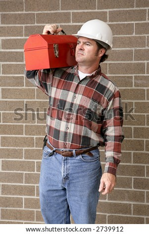 A handsome construction worker carrying his toolbox on his shoulder and looking toward the future. - stock photo