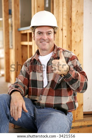 A handsome construction worker giving a thumbs-up sign.  Authentic construction worker on actual construction site. - stock photo