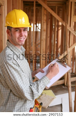A handsome construction worker with a clipboard at a home building site - stock photo