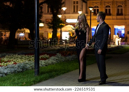 A handsome couple on a date night walk in the city - stock photo