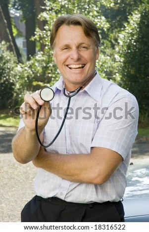 A handsome doctor in his forties is smiling as he holds out his stethoscope towards the camera
