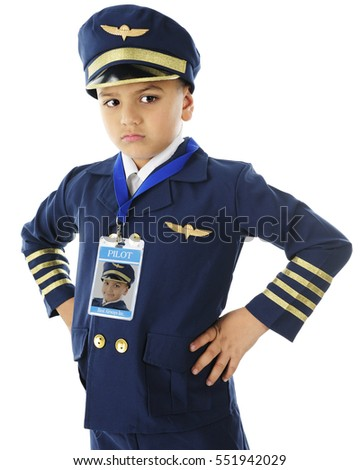 A handsome elementary boy unhappy in his airline pilot uniform.  On a white background.