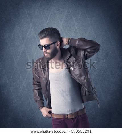 A handsome fashion model with beard standing in front of fancy background and making funny faces while using a vintage camera concept - stock photo